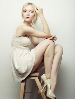 Hermosa modelo rubia sentada en un taburete