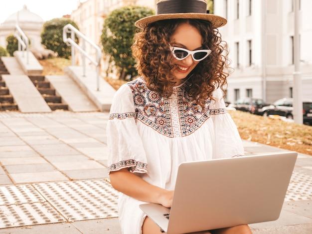 Hermosa modelo sonriente con peinado afro rizos en verano hipster vestido blanco y sombrero.