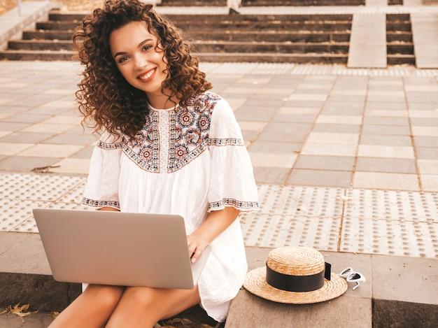 Hermosa modelo sonriente con peinado afro rizos vestido con vestido blanco hipster de verano.