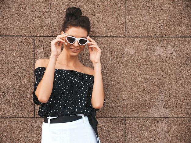 Hermosa modelo vestida con ropa elegante de verano. chica despreocupada sexy posando en la calle cerca de la pared. empresaria moderna de moda en gafas de sol divirtiéndose