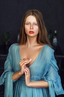 Hermosa modelo con vestido azul claro está posando en una habitación