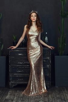 Hermosa modelo con vestido dorado está posando en una habitación oscura