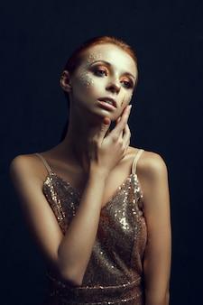 Hermosa modelo con vestido dorado está posando