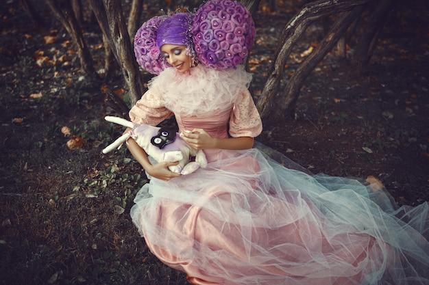 Hermosa modelo con vestido rosa posando con una peluca morada