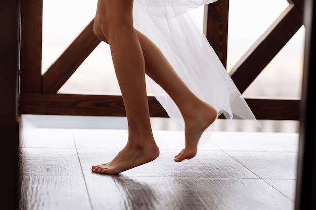 Hermosa y moderna novia de piernas largas y con velo en el balcón. mañana de boda
