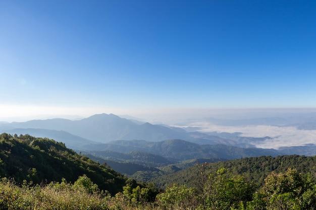 Hermosa montaña panorámica y niebla sobre fondo de cielo azul, en el norte de tailandia inthanon national park, provincia de chiang mai, panorama paisaje tailandia