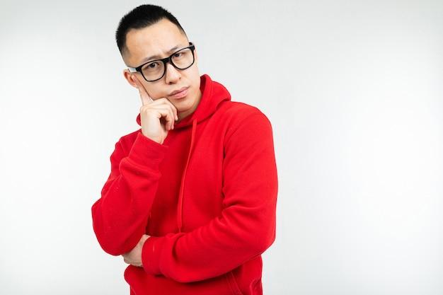 Hermosa morena asiática en suéter rojo y gafas para visión plantea en un blanco