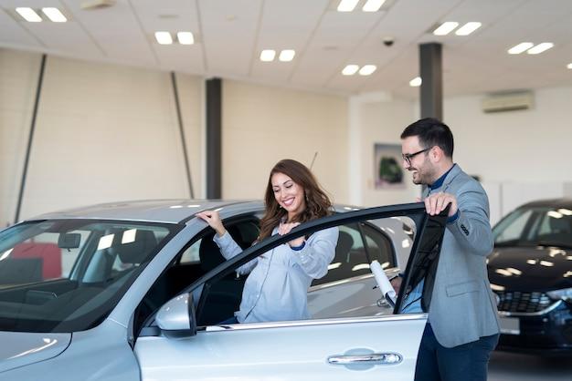 Hermosa morena atractiva entrando en un coche nuevo en el concesionario de vehículos.