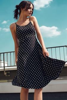 Hermosa morena brillante en vestido de moda posando en el techo de un edificio