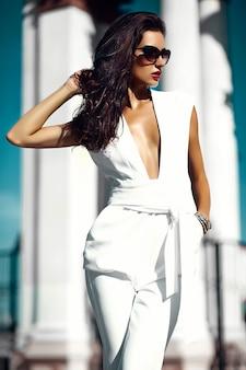 Hermosa morena en la calle vistiendo jersey blanco