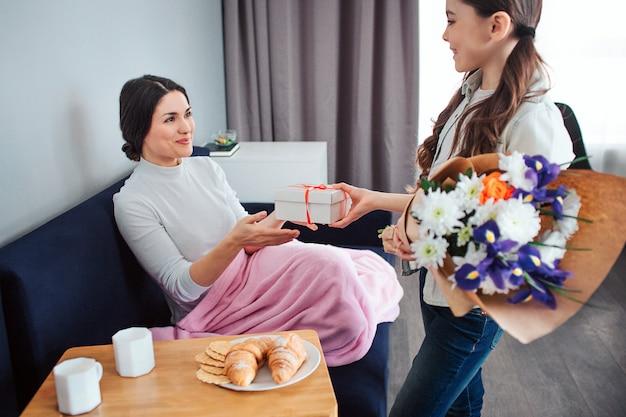 Hermosa morena caucásica madre e hija juntas en la habitación. joven mujer sentada en el sofá y presente con flores de niña. ella mira a mamá y sonríe. felices juntos.