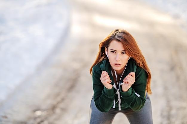 Hermosa morena caucásica en ropa deportiva descansando en el sendero y tratando de calentar. invierno gimnasio al aire libre.