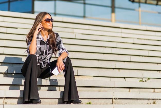 Hermosa morena chica caucásica escuchando la música con auriculares en las escaleras de la ciudad
