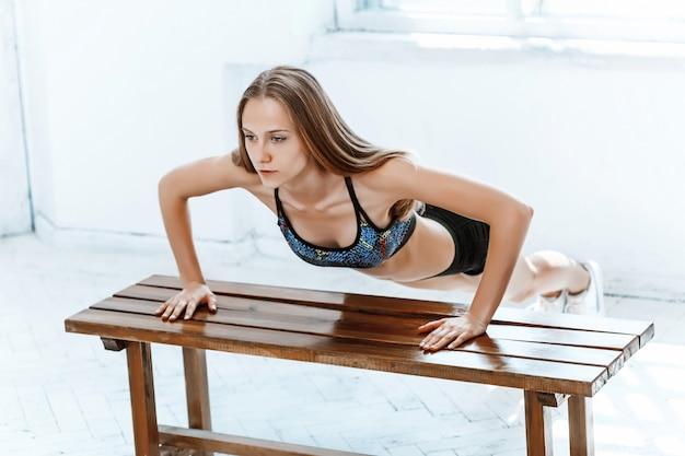 Hermosa morena delgada haciendo algunas flexiones en el gimnasio