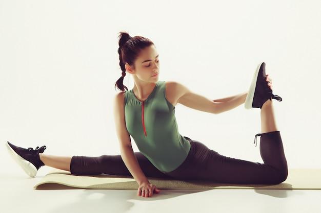 Hermosa morena delgada haciendo algunos ejercicios de estiramiento en un gimnasio