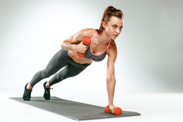 Hermosa morena delgada haciendo algunos ejercicios de estiramiento