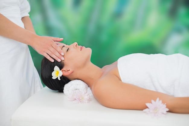 Hermosa morena disfrutando de un masaje de cabeza