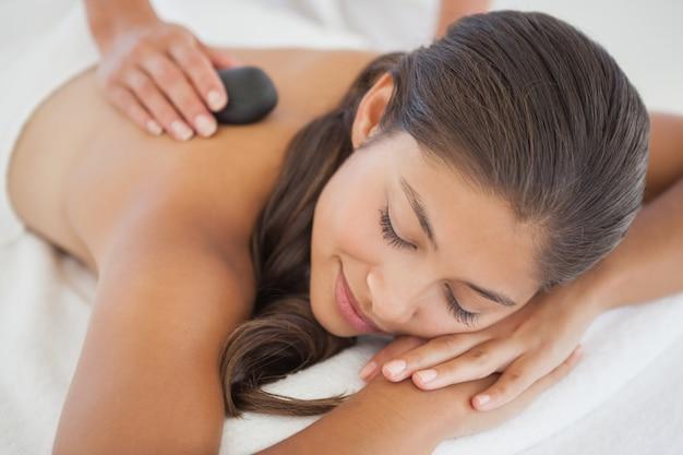 Hermosa morena disfrutando de un masaje con piedras calientes