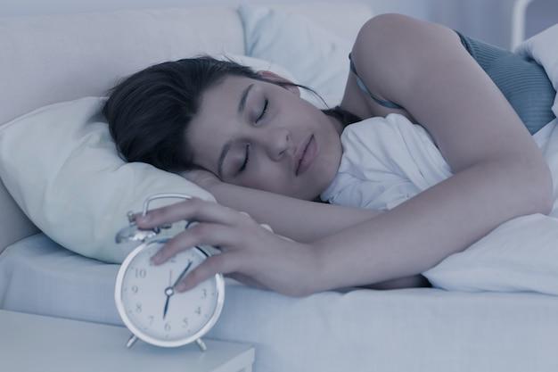 Hermosa morena durmiendo en su cama
