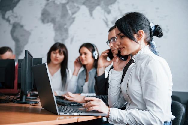 Hermosa morena en foco. jóvenes que trabajan en el centro de llamadas. se acercan nuevas ofertas