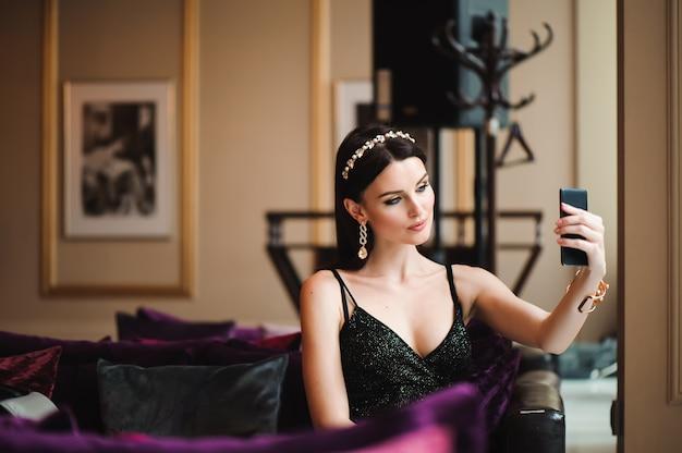 Hermosa morena en hotel con teléfono móvil