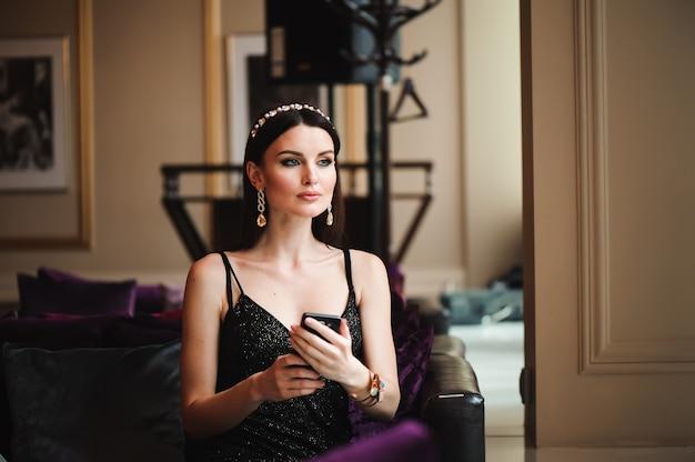 Hermosa morena en hotel con teléfono móvil.