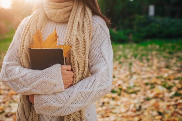 Hermosa morena joven sentada en un otoño caído deja en un parque, leyendo un libro.