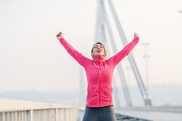 Hermosa morena levantando los brazos en el aire y sintiéndose libre después de correr en el puente. horario de invierno, concepto de estilo de vida saludable.