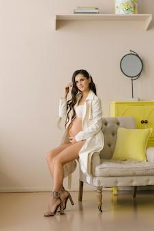Hermosa morena linda y elegante embarazada en lencería y ve en el borde de la silla en la sala de estar o dormitorio en colores pastel y sonrisas