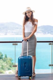 Hermosa morena con el pelo rizado en un sombrero ligero posando mientras está de pie en la terraza con una maleta en sus manos.