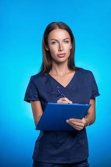 Hermosa morena con el pelo en un traje quirúrgico azul posando de pie sobre un fondo azul, con una carpeta azul y un bolígrafo en sus manos. escribe con un bolígrafo en una carpeta azul.