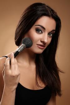 Hermosa morena con pincel de maquillaje