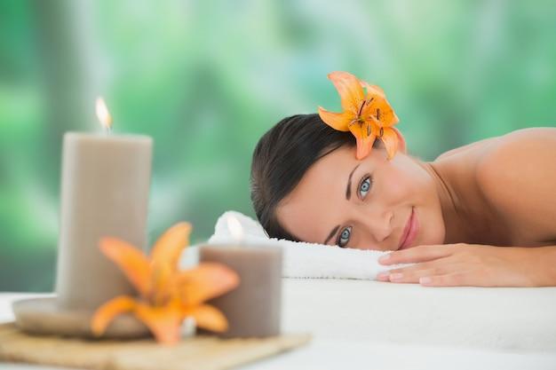 Hermosa morena relajante en mesa de masaje sonriendo a la cámara