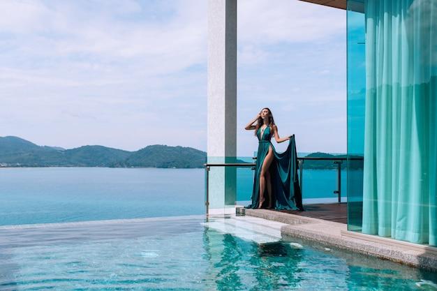 Hermosa morena semidesnuda con un vestido de noche azul posando con los ojos cerrados cerca de la piscina