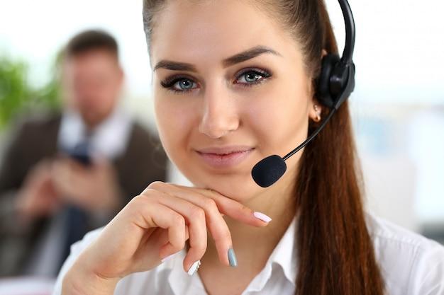 Hermosa morena sonriente empleado de call center en el trabajo
