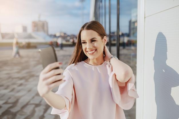 Hermosa morena sonriente vestida elegante de pie al aire libre y tomando selfie