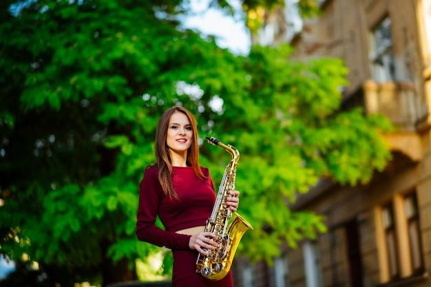 Hermosa morena toca el saxofón en el parque