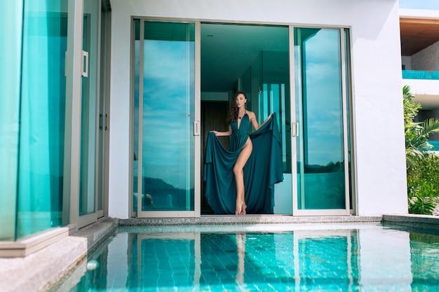 Hermosa morena en vestido de noche azul posando de pie cerca de la piscina en una villa