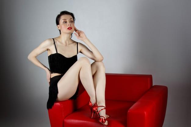 Una hermosa morena con zapatos rojos se sienta en un sillón rojo sobre un fondo gris.