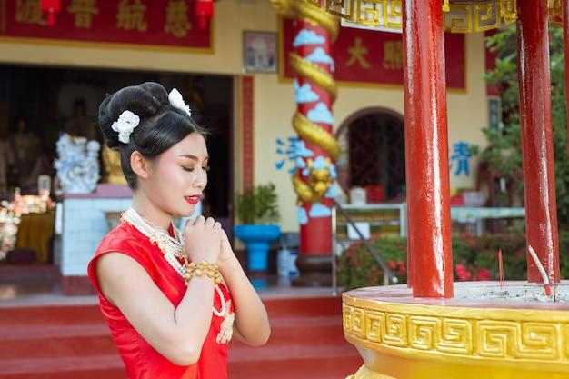 Una hermosa muchacha asiática que lleva un culto rojo