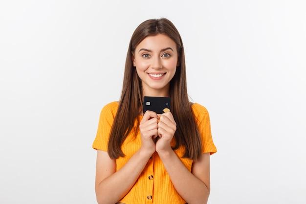 Hermosa muchacha sonriente amistosa confidente que muestra la tarjeta negra en la mano, aislada sobre blanco.