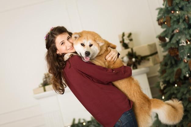 Hermosa mujer abraza, abraza con su perro akita inu, en una cómoda de árbol de navidad con velas en una habitación decorada
