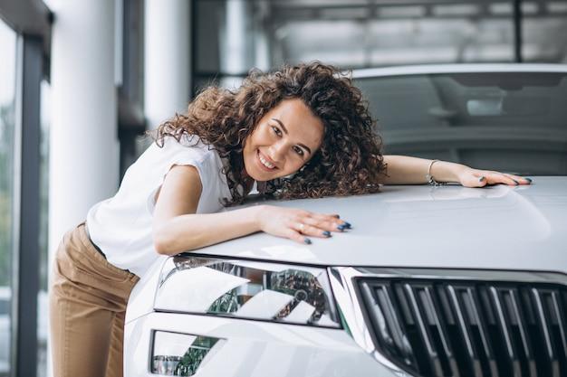 Hermosa mujer abrazando un auto