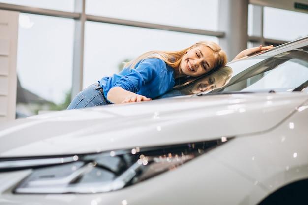 Hermosa mujer abrazando un automóvil en un showrrom de automóviles