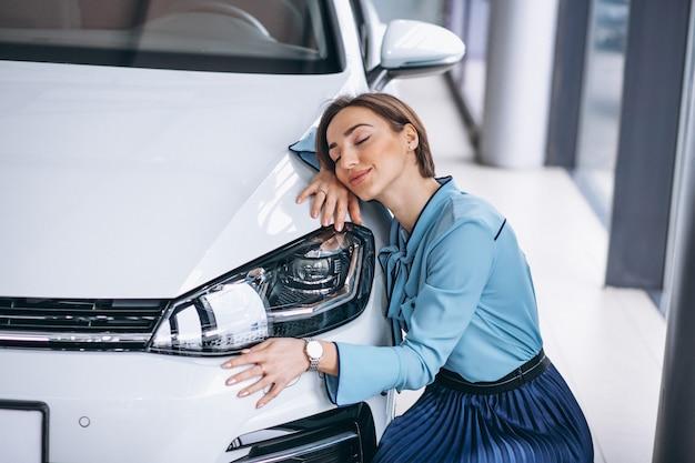 Hermosa mujer abrazando un coche