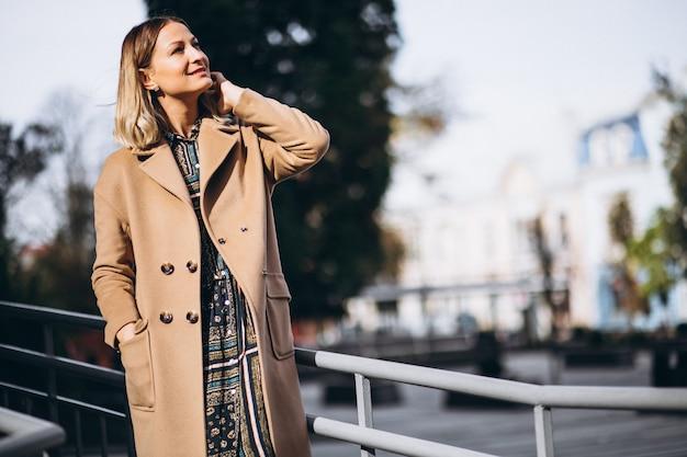Hermosa mujer en un abrigo beige afuera en el parque