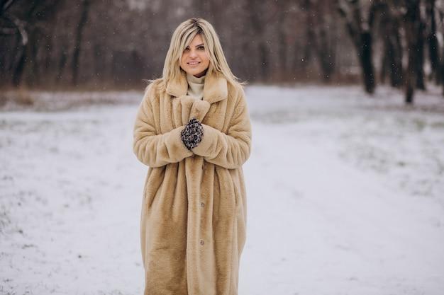 Hermosa mujer en abrigo de invierno caminando en el parque lleno de nieve