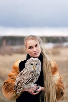 Hermosa mujer en un abrigo de piel con un búho en el brazo. rubia