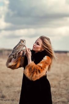 Hermosa mujer en un abrigo de piel con un búho en el brazo.