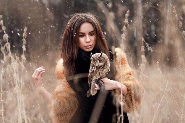 Hermosa mujer en un abrigo de piel con un búho en mano